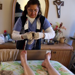 A home-care worker helps her client get dressed.