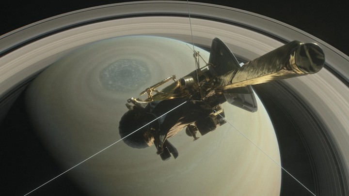 An illustration of Cassini above Saturn's northern hemisphere during its final orbits