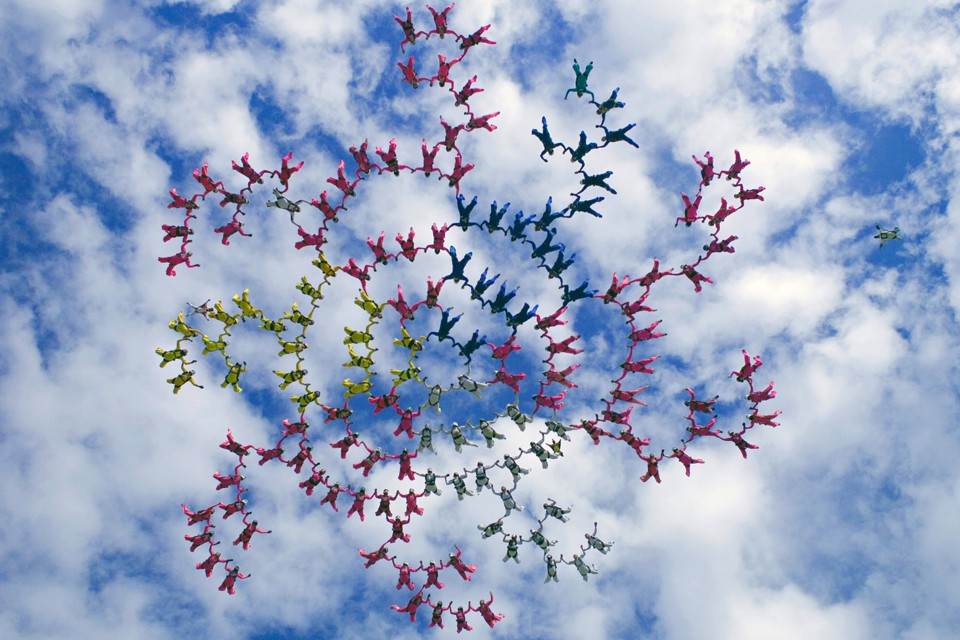 A spiraling skydiving formation against a partly cloudy sky
