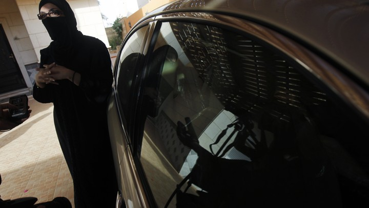 A veiled Saudi driver stands next to her car