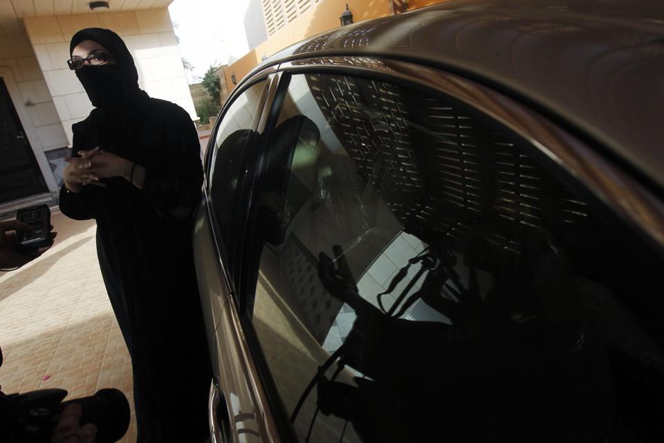 A veiled Saudi driver stands next to her car