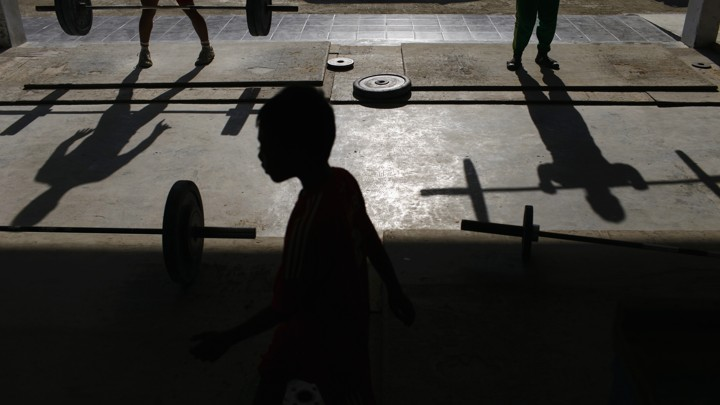 Silhouettes of boys lifting weights
