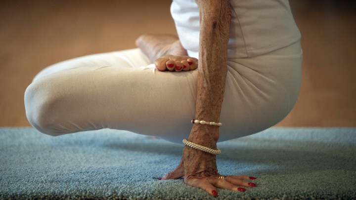 An elderly white person in white clothing with red nail polish does an exercise on a blue mat.