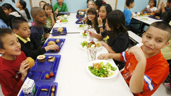 Young students at a cafeteria table eat lunch