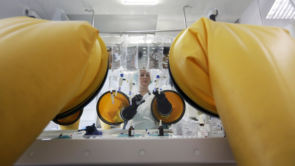 A dispensing chemist prepares drugs for a chemotherapy treatment in a sterile room.