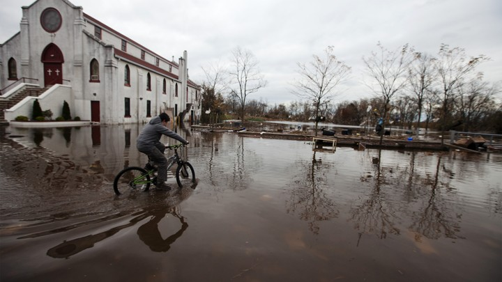A boy rides his bicycle through floodwaters in the New Dorp Beach neighborhood of Staten Island, New York, on November 1, 2012.