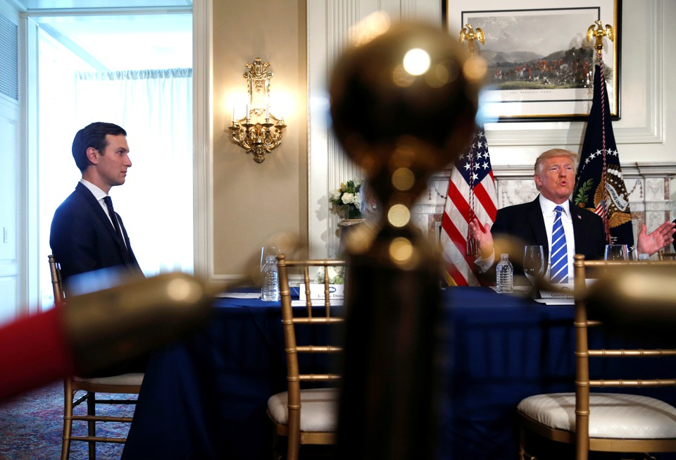 Jared Kushner sits at a table with Donald Trump.