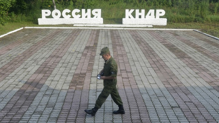"""A guard walks along a platform past signs, which read """"Russia"""" and """"DPRK."""""""