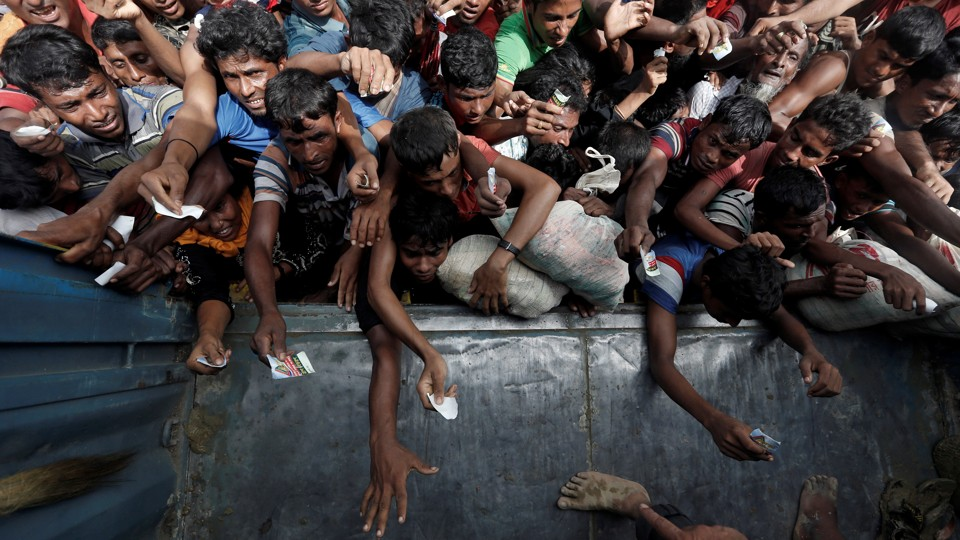 Rohingya refugees wait to receive aid in Cox's Bazar.