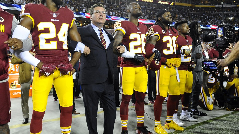 The Washington football team owner Daniel Snyder stands with the players Josh Norman, Bashaud Breeland, and D.J. Swearinger during the playing of the national anthem before a game.
