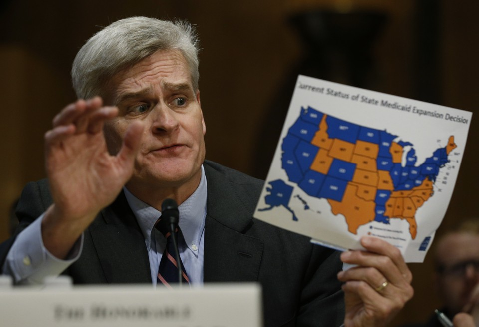 Senator Bill Cassidy of Louisiana holds a map of projected federal spending on health care, by state.