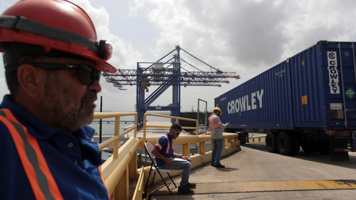Workers unload a barge at the port of San Juan, Puerto Rico.