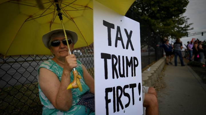 A woman holds a sign during demonstrations as U.S. President Donald Trump delivers a speech on tax reform.