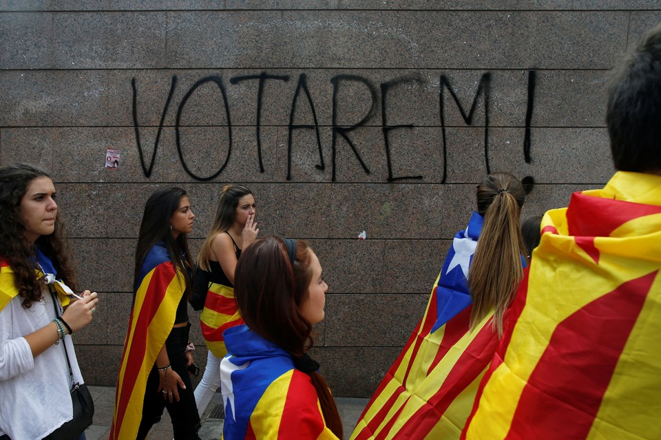 "Students wear Esteladas (Catalan separatist flag) during a demonstration in front of a graffiti on the wall that reads, ""We will vote!"""