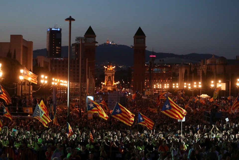 People wave Catalan separatist flagsat a rally