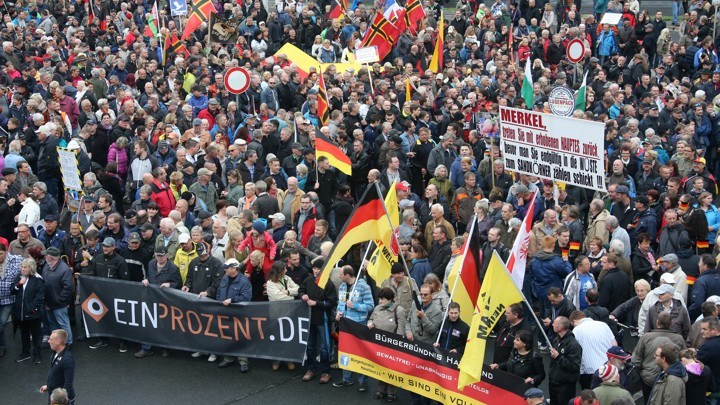 "Supporters of the anti-Islam movement ""Patriotic Europeans Against the Islamization of the West"" (PEGIDA) march with flags."