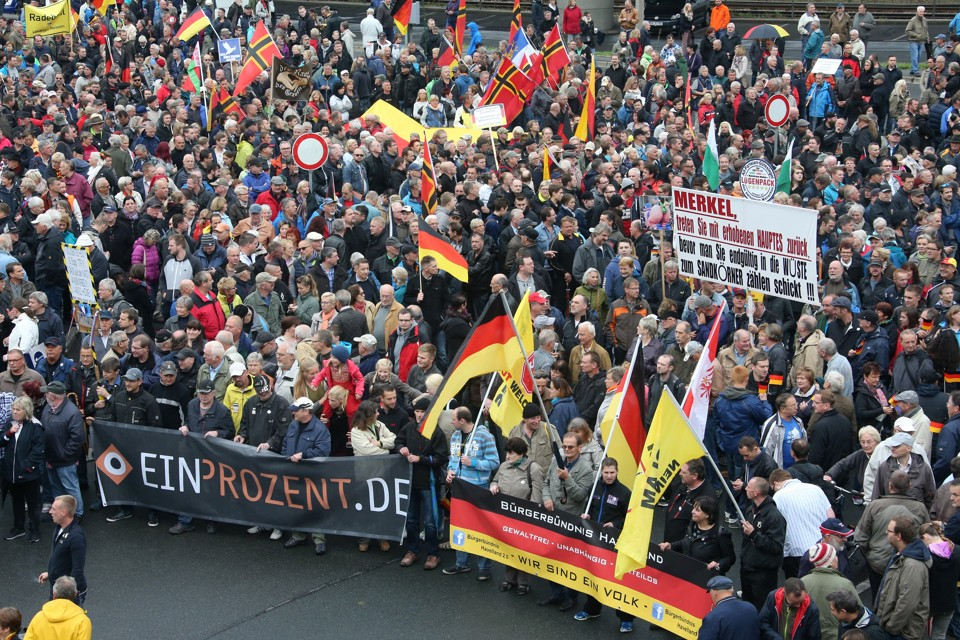 """Supporters of the anti-Islam movement """"Patriotic Europeans Against the Islamization of the West"""" (PEGIDA) march with flags."""