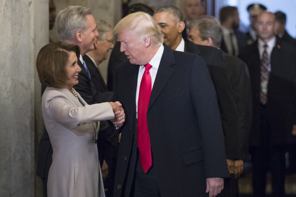 Donald Trump shakes hands with Nancy Pelosi.