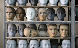 Mannequin heads sitting on a shelf in a factory