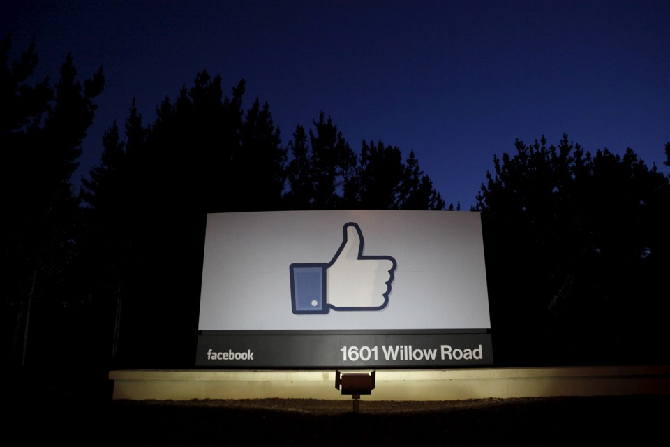 "A Facebook ""like"" symbol illuminated at night on a sign that says ""1601 Willow Road"""