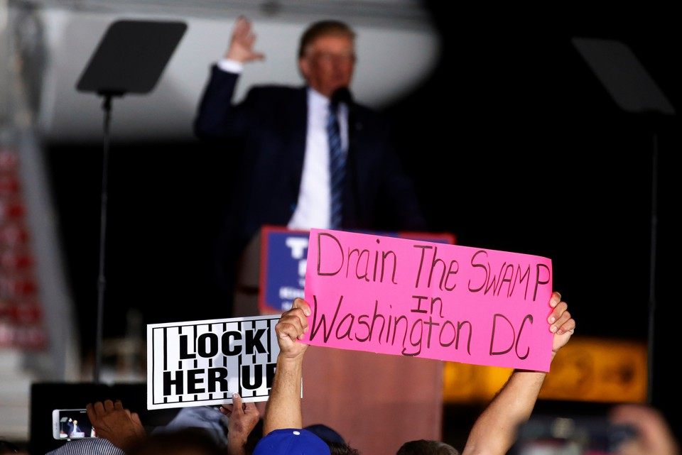 "Trump supporters hold up a ""Drain the Swamp"" sign."