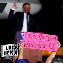 """Trump supporters hold up a """"Drain the Swamp"""" sign."""