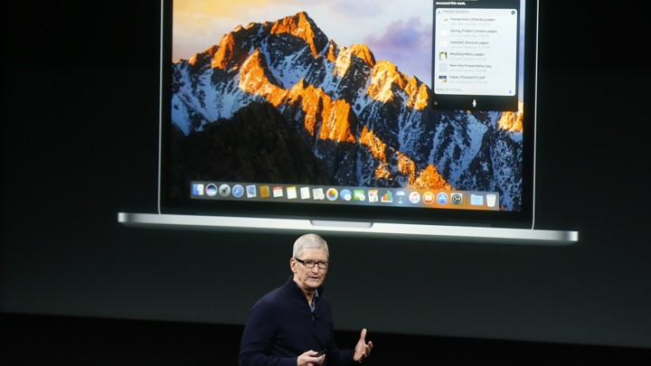 Tim Cook stands in front of a projected image of an Apple laptop.