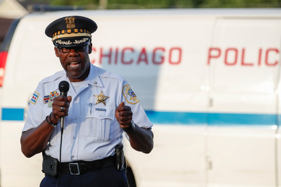 Chicago Police District Commander Kenneth Johnson, wearing his uniform and holding a microphone, speaks during an anti-violence rally in Chicago in July.