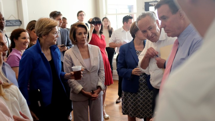 Nancy Pelosi and Elizabeth Warren stand in a room with others.