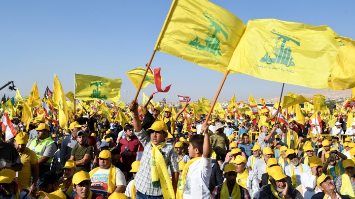 Supporters of Lebanon's Hezbollah leader Sayyed Hassan Nasrallah display Hezbollah and Lebanese flags.