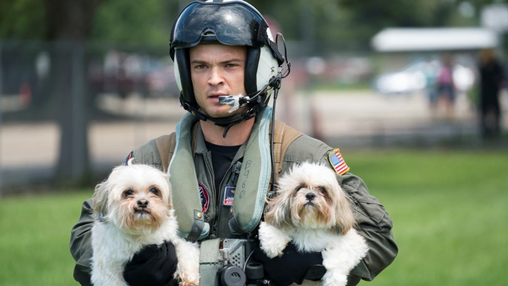 A Naval Aircrewman carrying two dogs.