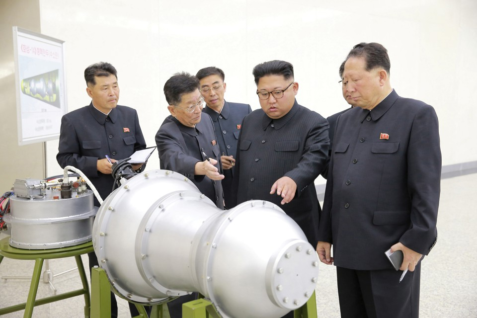 Kim Jong Un and North Korean officials examine what appears to be a missile