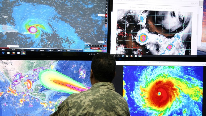A man in camouflage stands in front of computer screens showing images of Hurricane Irma.