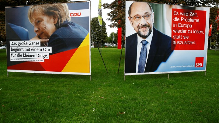 Election campaign posters show Angela Merkel and Martin Schulz side by side on the grass.