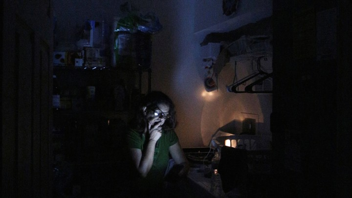 A woman reads from a mobile device in a dark room.