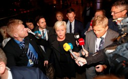 Siv Jensen walks out surrounded by reporters with microphones.