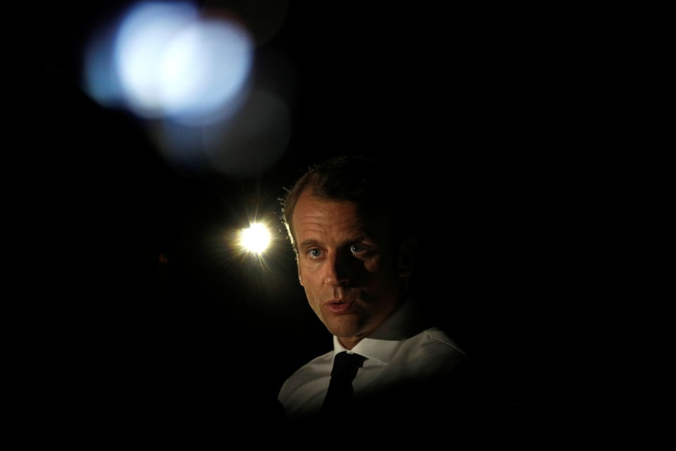 President Emmanuel Macron talks with lights in the background.