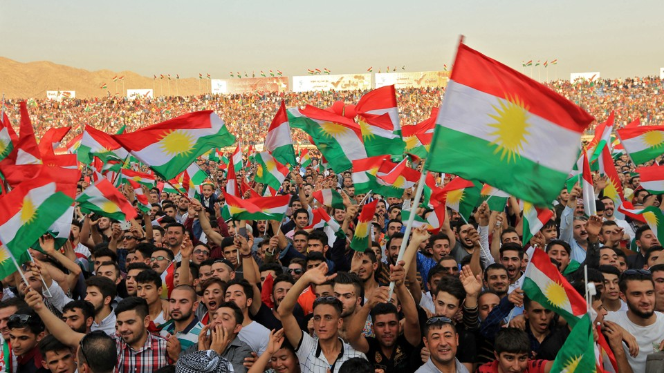 Kurdish people attend a rally and wave Kurdish flags.