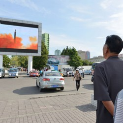 North Koreans watch news report showing North Korea's Hwasong-12 intermediate-range ballistic missile launch on an electronic screen.