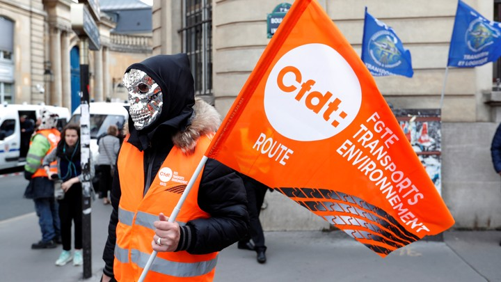 A masked demonstrator holds a flag of the French Democratic Confederation of Labour union (CFDT) in Paris during a national protest against the government's labour reforms on September 18, 2017.
