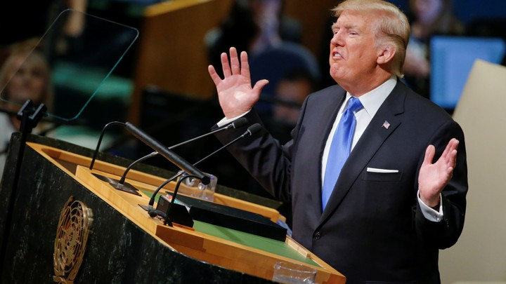President Donald Trump is shown on a large screen.