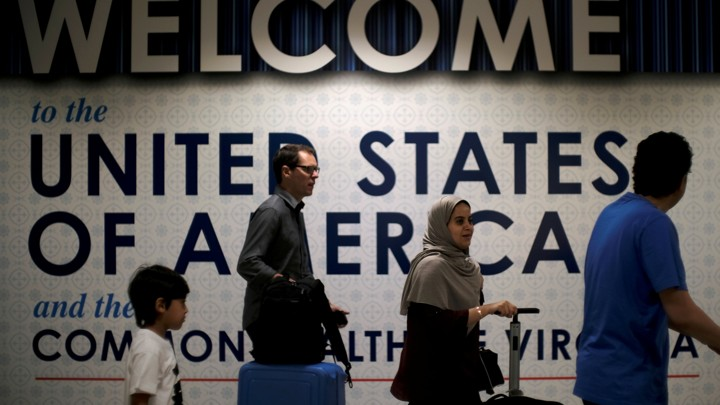 "Four people walk past a sign that says ""Welcome to the United States"""