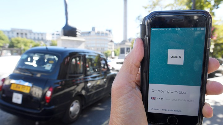 A person holds a phone with the Uber app in front of a black cab.