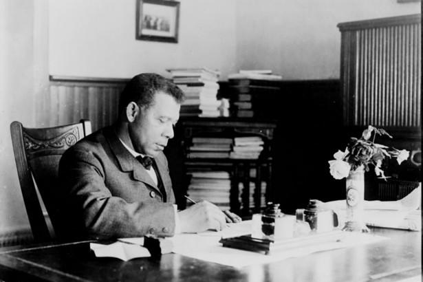 Booker T. Washington sits writing at his desk