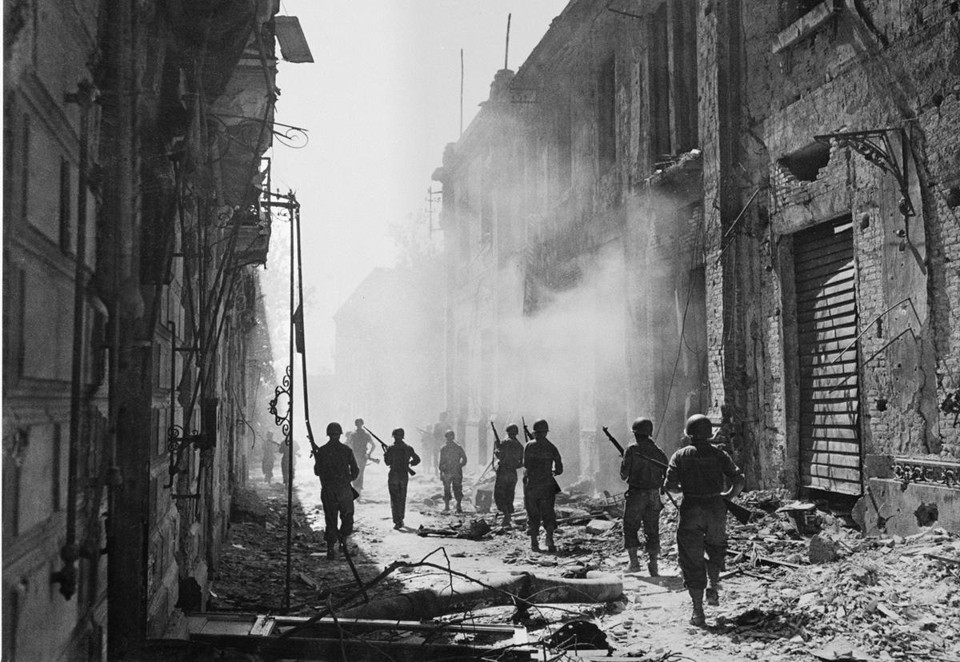 A photograph of soldiers in a street full of rubble