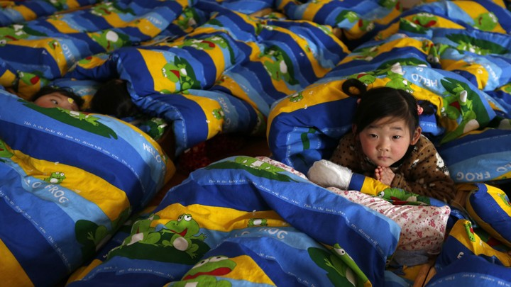 A child looks up at the camera while other children nap around her.