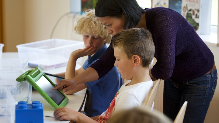 A teacher stands next to two students and looks at something on an iPad with them.