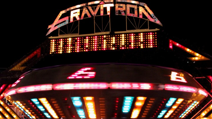A gravitron ride at a carnival at night