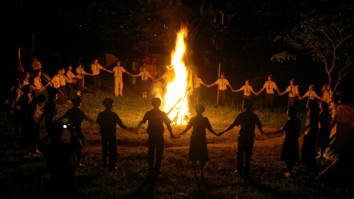 Children in scout uniforms hold hands around a bonfire