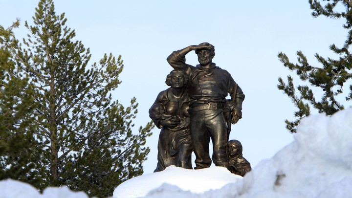A bronze statue of travelers surrounded by snow